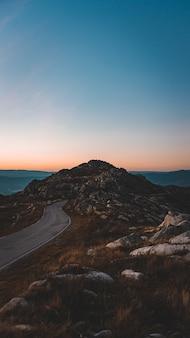 美しい夕焼け空の下の岩だらけの洞窟に通じる狭い道