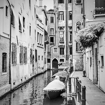이탈리아 베니스에 정박된 모터보트가 있는 좁은 운하. 흑백 이미지
