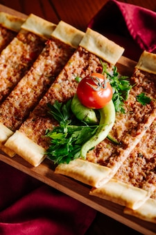 Narrow sliced traditional turkish lahmacun with herbs and vegetables.
