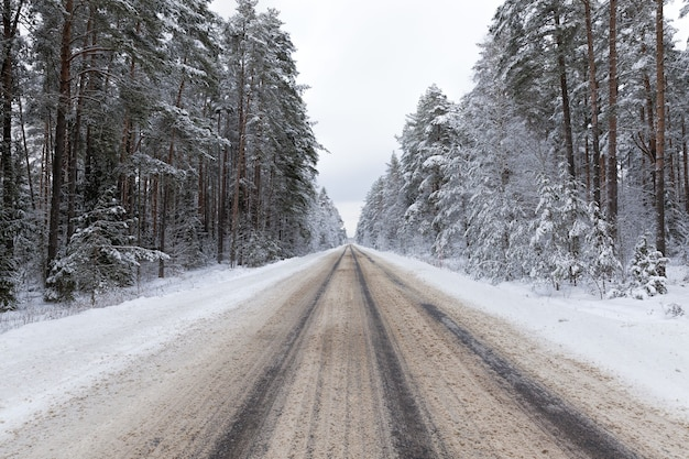 Narrow snow-covered winter road for car traffic, cloudy sky on the road, snow on the road melts from car traffic