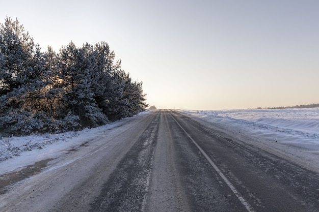 Narrow snow-covered winter road for driving cars through the forest, cloudy sky on the road, snow on the road crumples and melts from the movement of cars