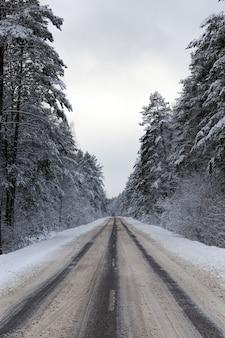 森の中を車を運転するための狭い雪に覆われた冬の道、道路の曇り空、道路の雪はしわくちゃになり、車の動きから溶けます
