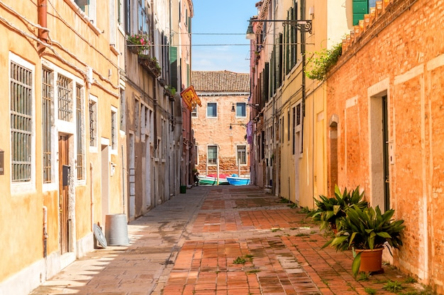 Narrow street of murano with colorful houses and plants in early morning in venice, italy.
