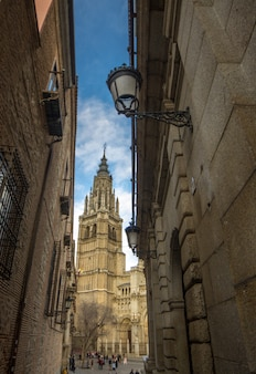 Narrow street of toledo in which the tower of the cathedral of toledo is seen.