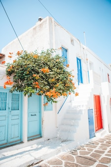 The narrow streets of the island with blue balconies, stairs and flowers in greece.