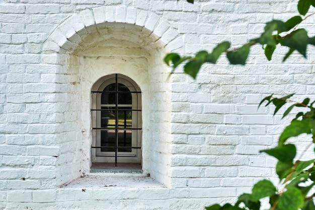 Узкое окно в расписной кирпичной стене старинного здания русского монастыря