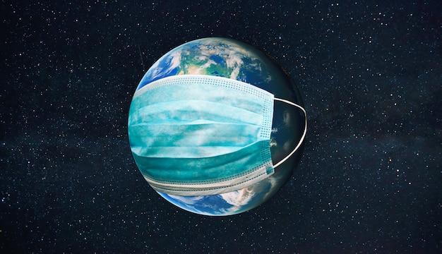 地球は宇宙で防護マスクを着用しています。検疫、ウイルスやパンデミックからの保護の概念。 nasaから提供されたこの画像の要素