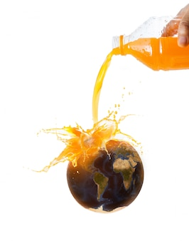 Nasaから世界地図画像ソースと新鮮な熟したオレンジ色の果物にオレンジジュースを注ぐ女性の手