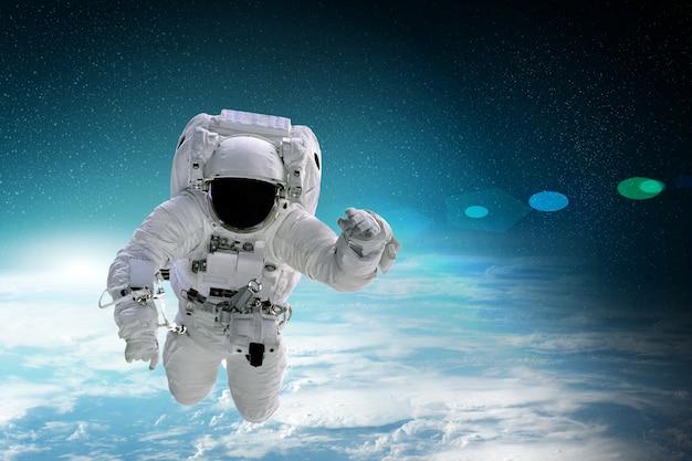 宇宙飛行士は宇宙で地球上を飛ぶ。 nasaによって提供されたこのイメージの要素