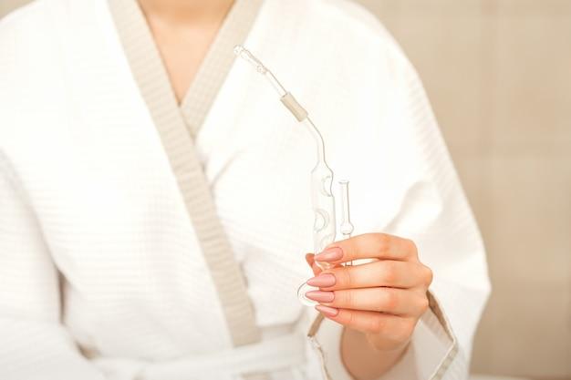 Назальный ингалятор эфирного масла maholda в руках молодой женщины в спа-центре