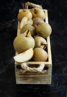 暗い背景の木製の箱の中のナシ梨(リンゴ梨またはアジア梨)