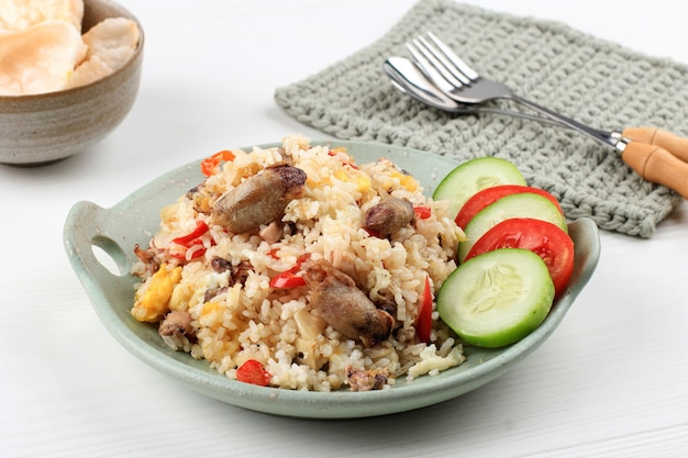 Наси горенг cumi asin (жареный рис с солеными кальмарами), приготовленный с чили, пряный и вкусный. типичная индонезийская домашняя еда. подается на зеленой тарелке, изолированной на белом фоне
