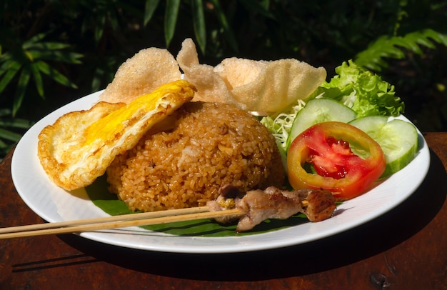 나시 고렝, 볶음밥, 인도네시아 전통 음식, 닭고기 달걀과 야채를 하얀 접시에 담았습니다. 인도네시아 요리.
