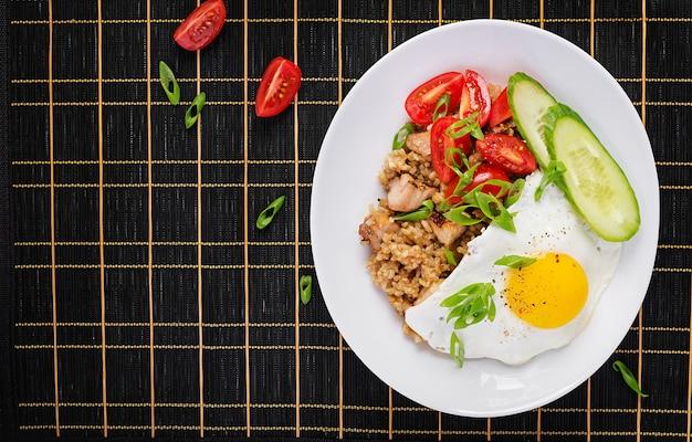 ナシゴレン。暗い背景にインドネシアのチキンチャーハン。ナシゴレンは、ご飯、鶏肉、玉ねぎ、卵、野菜を使ったインドネシア料理です。上面図、上、コピースペース