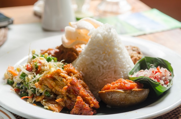 Nasi lemack style dish fresh vegetables nuts and fish with rice popular across indonesia