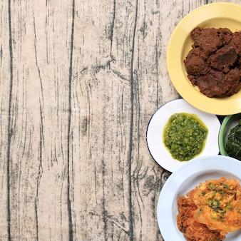 ナシパダンインドネシア料理、ルンダン、卵、ラドムド。木製の背景にスペースをコピー