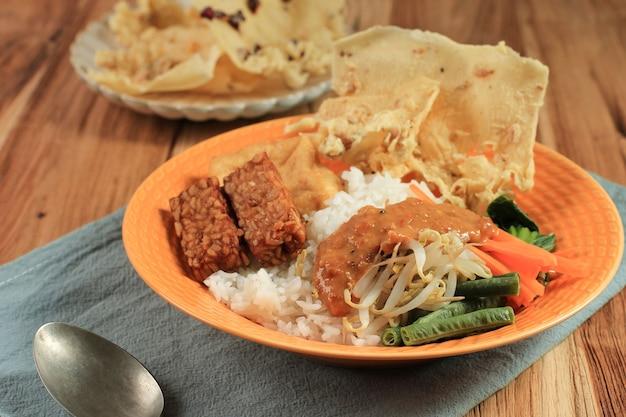 나시 페셀. 야채 샐러드, 땅콩 소스 드레싱, 템페, 두부 두부, 페엑 크래커를 곁들인 찐 쌀의 전통적인 자바 쌀 요리. pecel madiun은 가장 인기 있는 변형입니다.