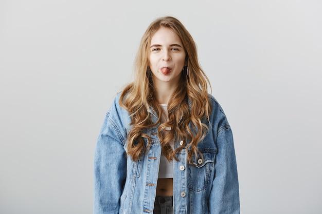 誰かをからかう舌を示す厄介なかわいいブロンドの女の子