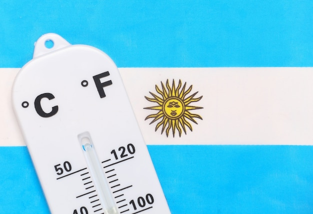 National ambient temperature control. weather thermometer on background of argentina flag. global warming concept