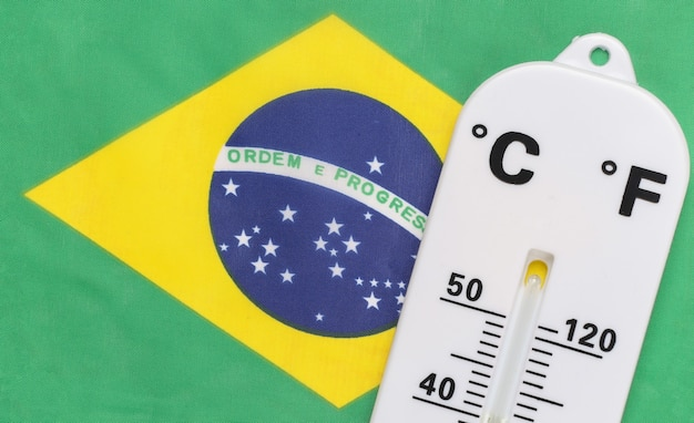 National ambient temperature control. weather thermometer on the background of brazil flag. global warming concept