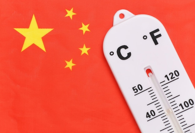 National ambient temperature control. weather thermometer on the background of the flag of china. global warming concept
