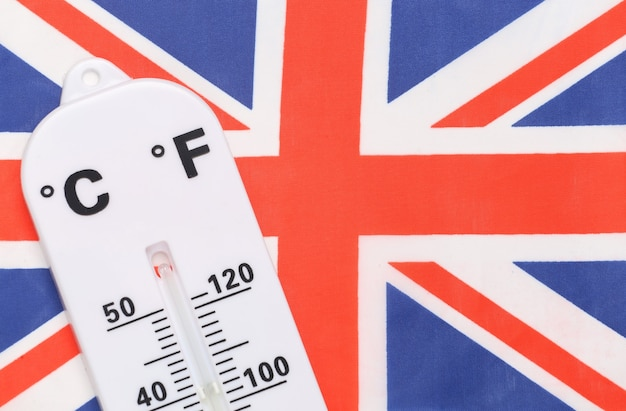 National ambient temperature control. weather thermometer on background of great britain flag. global warming concept