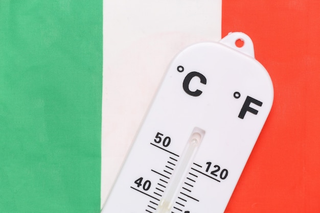 National ambient temperature control. weather thermometer on the background of italy flag. global warming concept
