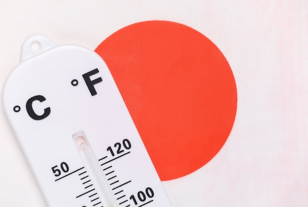 National ambient temperature control. weather thermometer on background of japanese flag. global warming concept
