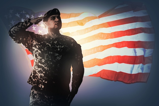 National anthem is played army ranger in universal camouflage pattern uniforms is standing to attention and saluting proudly service to his country concept national holidays veterans day