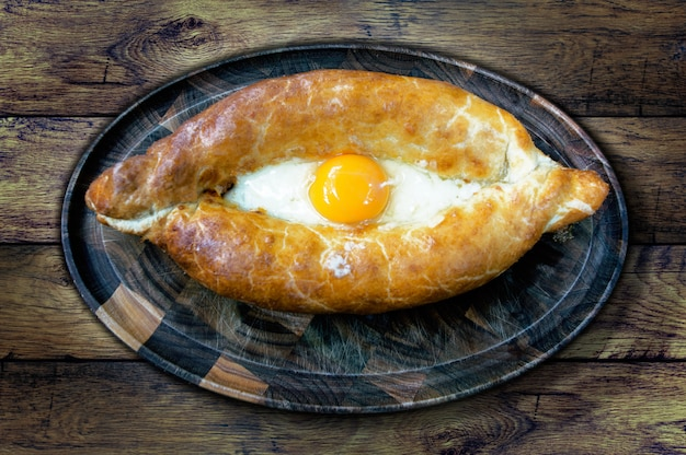 The national dish khachapuri on the board on the background of the old table, top view
