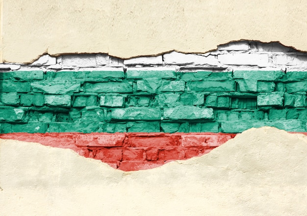 National flag of bulgaria on a brick background. brick wall with partially destroyed plaster, background or texture.