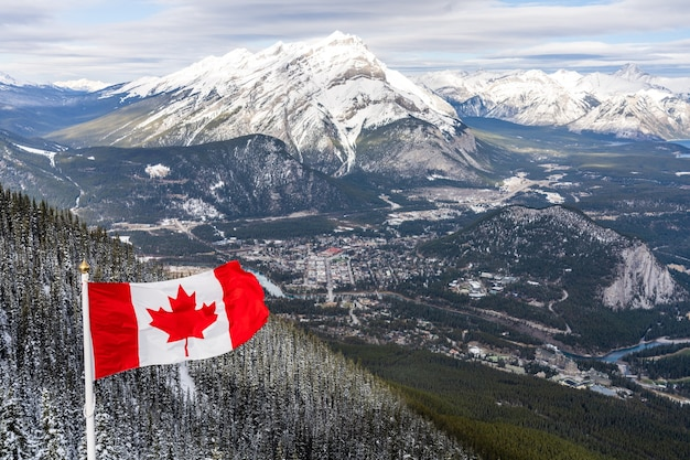 National flag of canada with canadian rocky mountains in winter banff national park canada Premium Photo