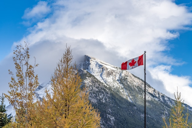 National flag of canada with mount rundle mountain range in a snowy sunny day banff national park