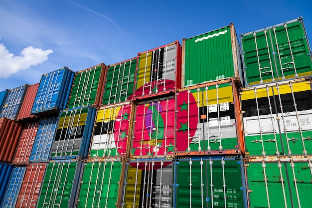 National flag of dominica on a large number of metal containers for storing goods stacked in rows