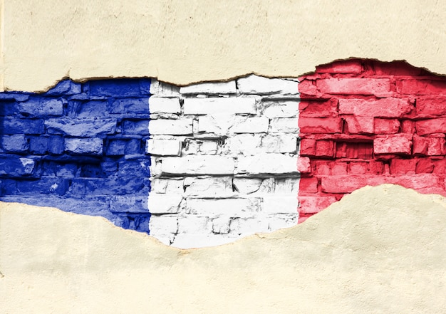 National flag of france on a brick background. brick wall with partially destroyed plaster, background or texture.