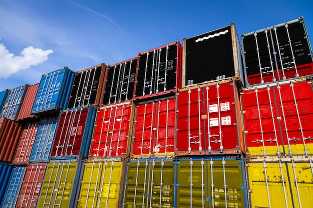 National flag of germany on a large number of metal containers for storing goods stacked in rows