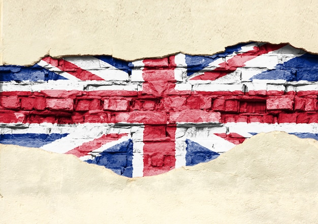 National flag of great britain on a brick background. brick wall with partially destroyed plaster, background or texture.