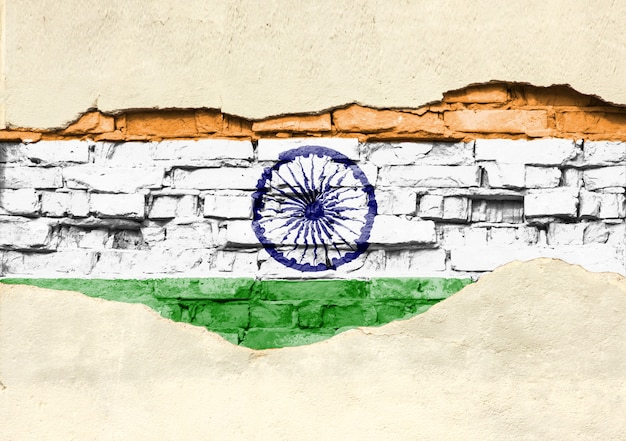National flag of india on a brick background. brick wall with partially destroyed plaster, background or texture.