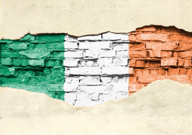 National flag of ireland on a brick background. brick wall with partially destroyed plaster, background or texture.