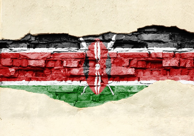 National flag of kenya on a brick background. brick wall with partially destroyed plaster, background or texture.