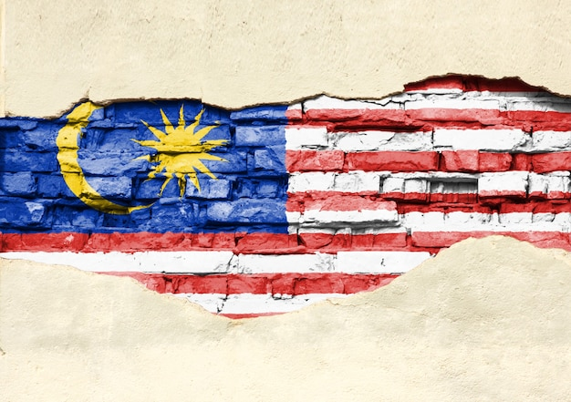 National flag of malaysia on a brick background. brick wall with partially destroyed plaster, background or texture.