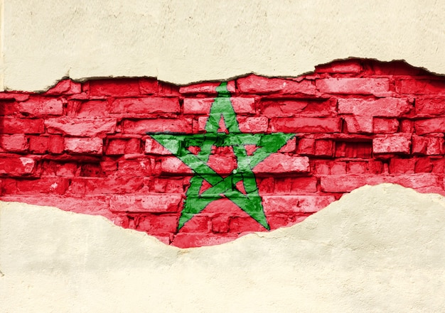 National flag of morocco on a brick background. brick wall with partially destroyed plaster, background or texture.