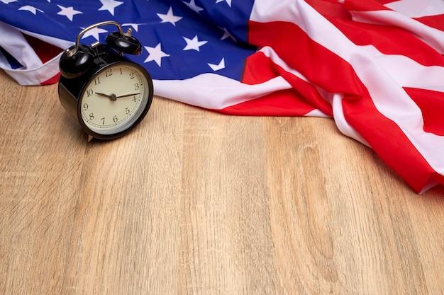 오래 된 나무 배경에 미국과 검은 알람 시계의 국기