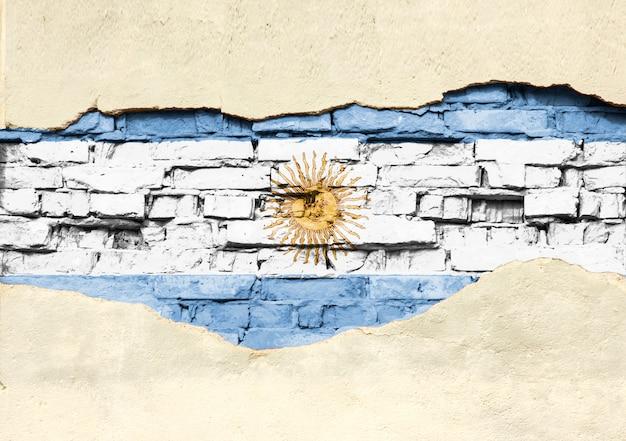 レンガの背景にアルゼンチンの国旗。部分的に破壊された漆喰、背景またはテクスチャのレンガの壁。