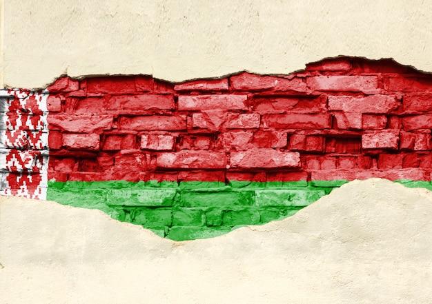 Государственный флаг беларуси на фоне кирпича. кирпичная стена с частично разрушенной штукатуркой, фоном или текстурой.
