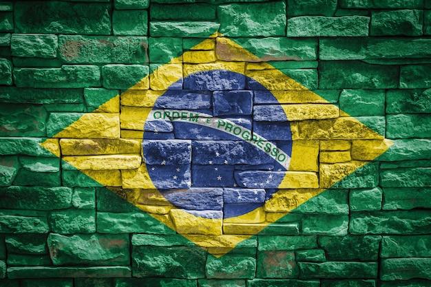 石の壁の背景にブラジルの国旗