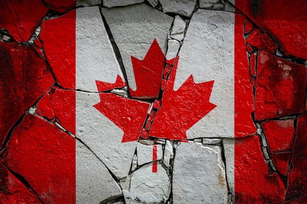 古い石の壁にペンキの色で描かれているカナダの国旗
