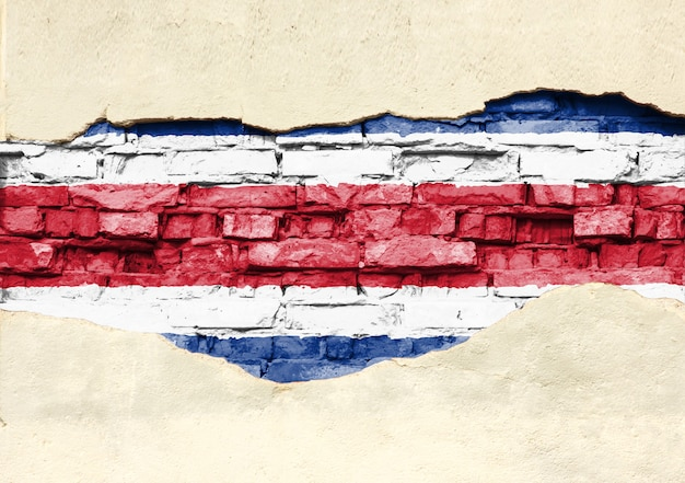 Национальный флаг коста-рики на фоне кирпича. кирпичная стена с частично разрушенной штукатуркой, фоном или текстурой.