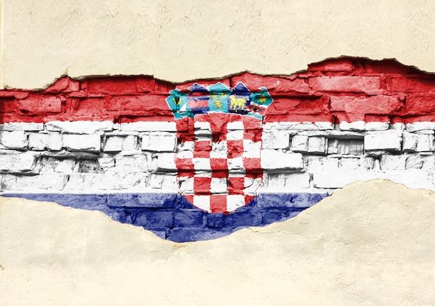 Национальный флаг хорватии на фоне кирпича. кирпичная стена с частично разрушенной штукатуркой, фоном или текстурой.