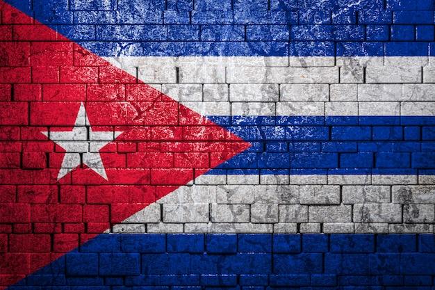 Национальный флаг кубы на фоне кирпичной стены.
